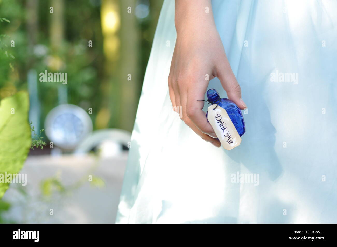 Drink me. Alice au Pays des Merveilles. Fille en robe bleue Photo Stock