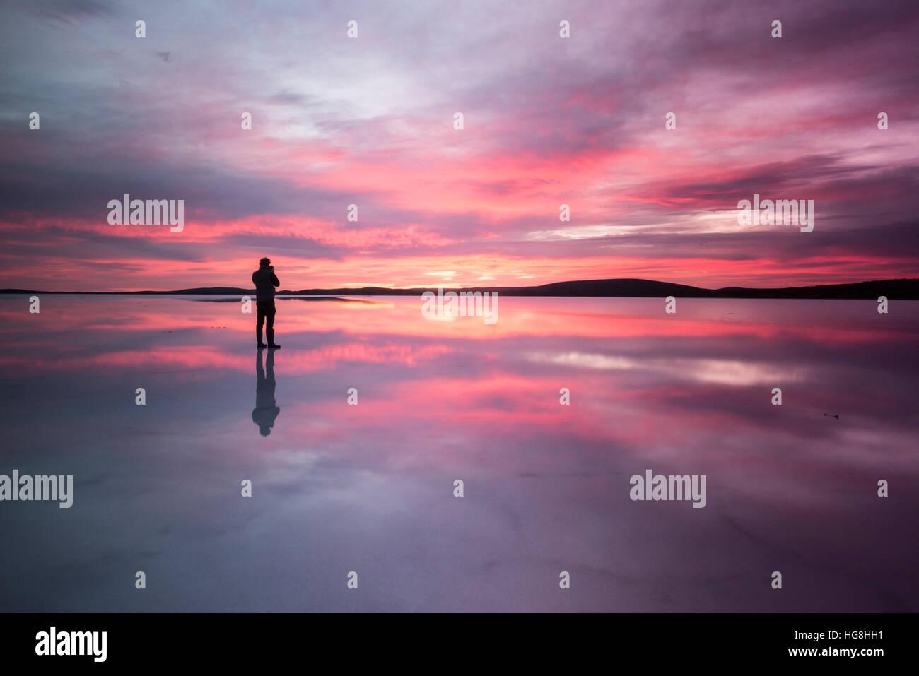 Une personne se tient sur un miroir reflète lake en regardant le coucher du soleil Photo Stock
