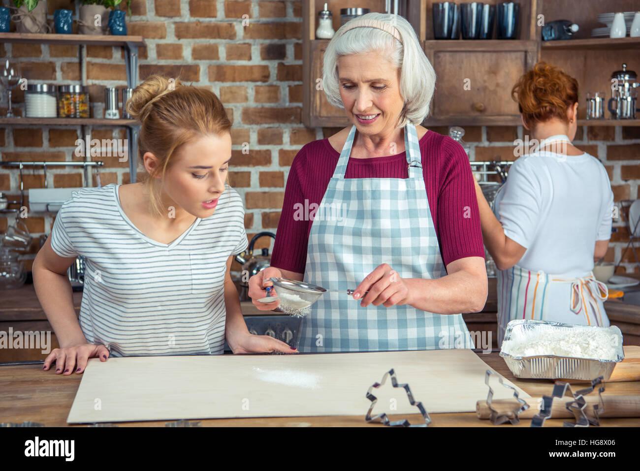 Grand-mère et petite-fille sasser la farine pour les cookies dans la cuisine Photo Stock