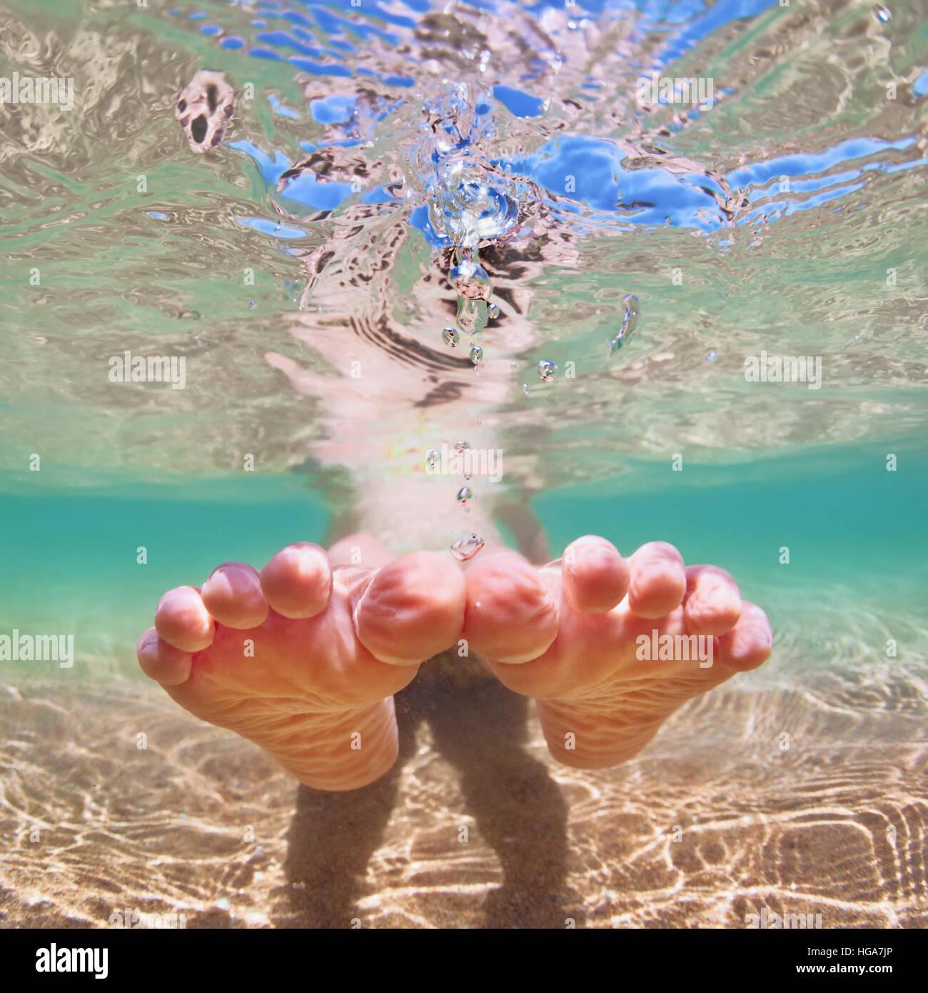 Photo sous-marine de l'heureux pied nu baby girl in nager avec piscine sur la mer. Vie familiale saine de l'eau, Photo Stock