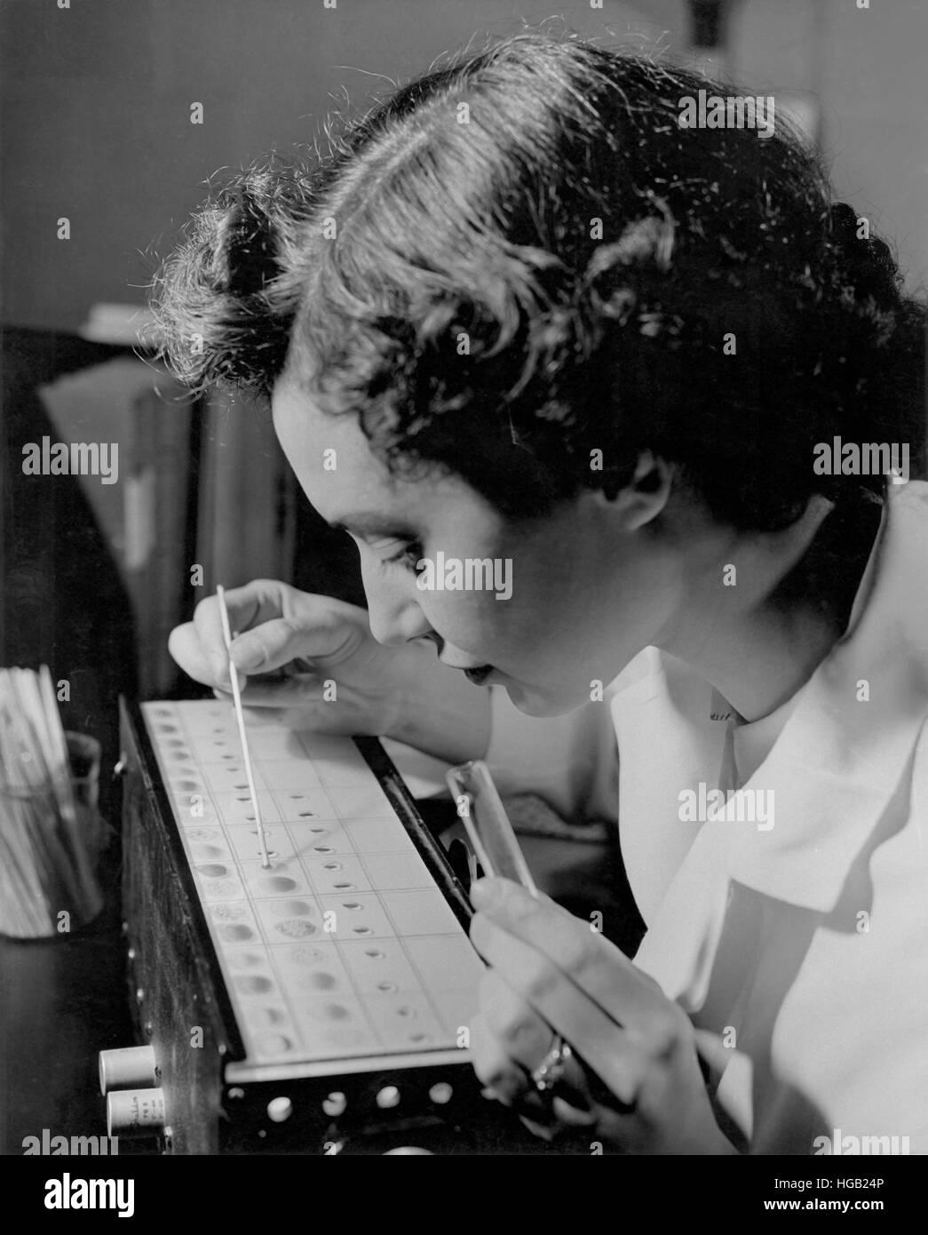 Technicien de laboratoire d'un échantillon de sang afficher la saisie, 1957. Photo Stock