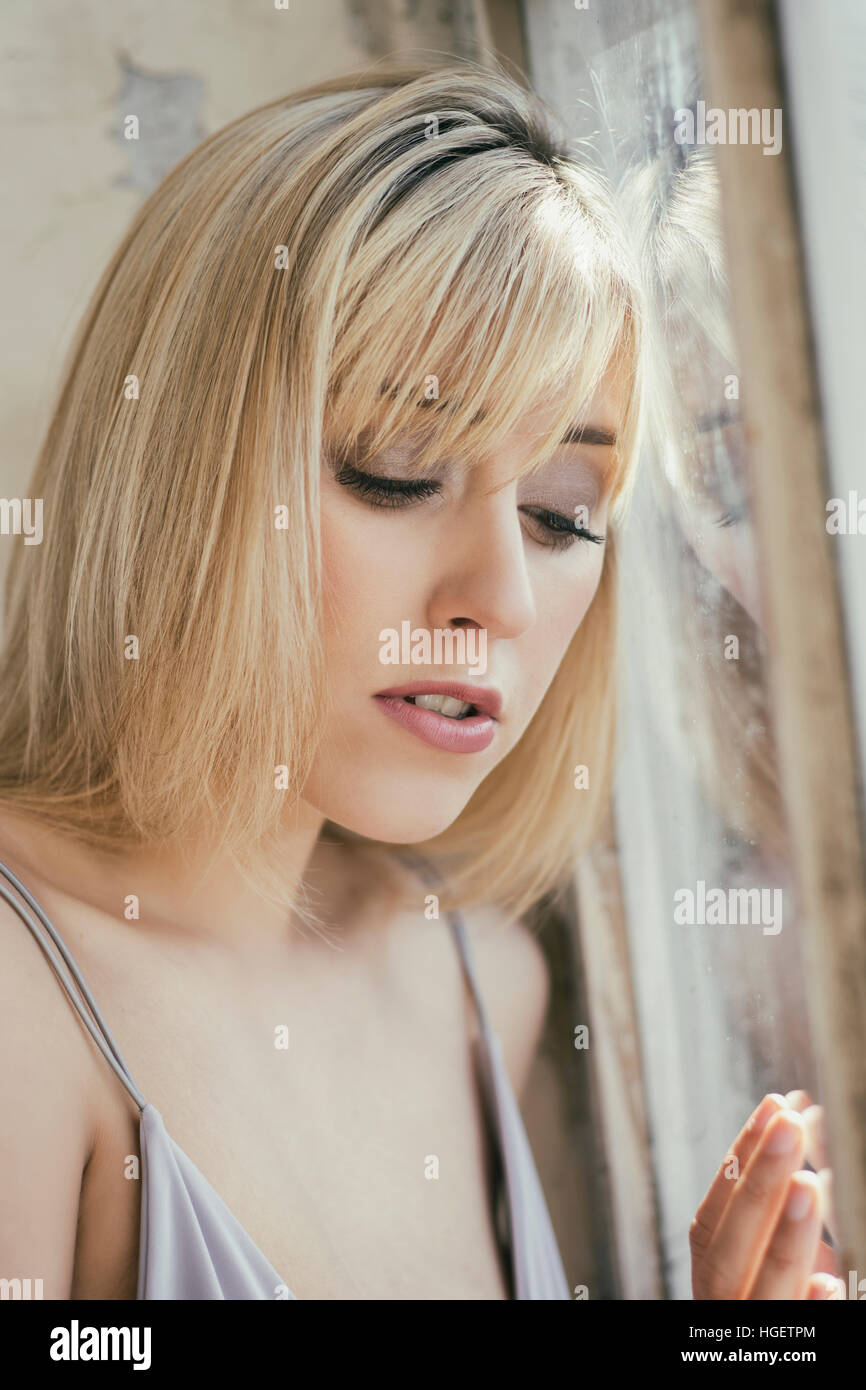 Triste belle femme regardant par la fenêtre Photo Stock