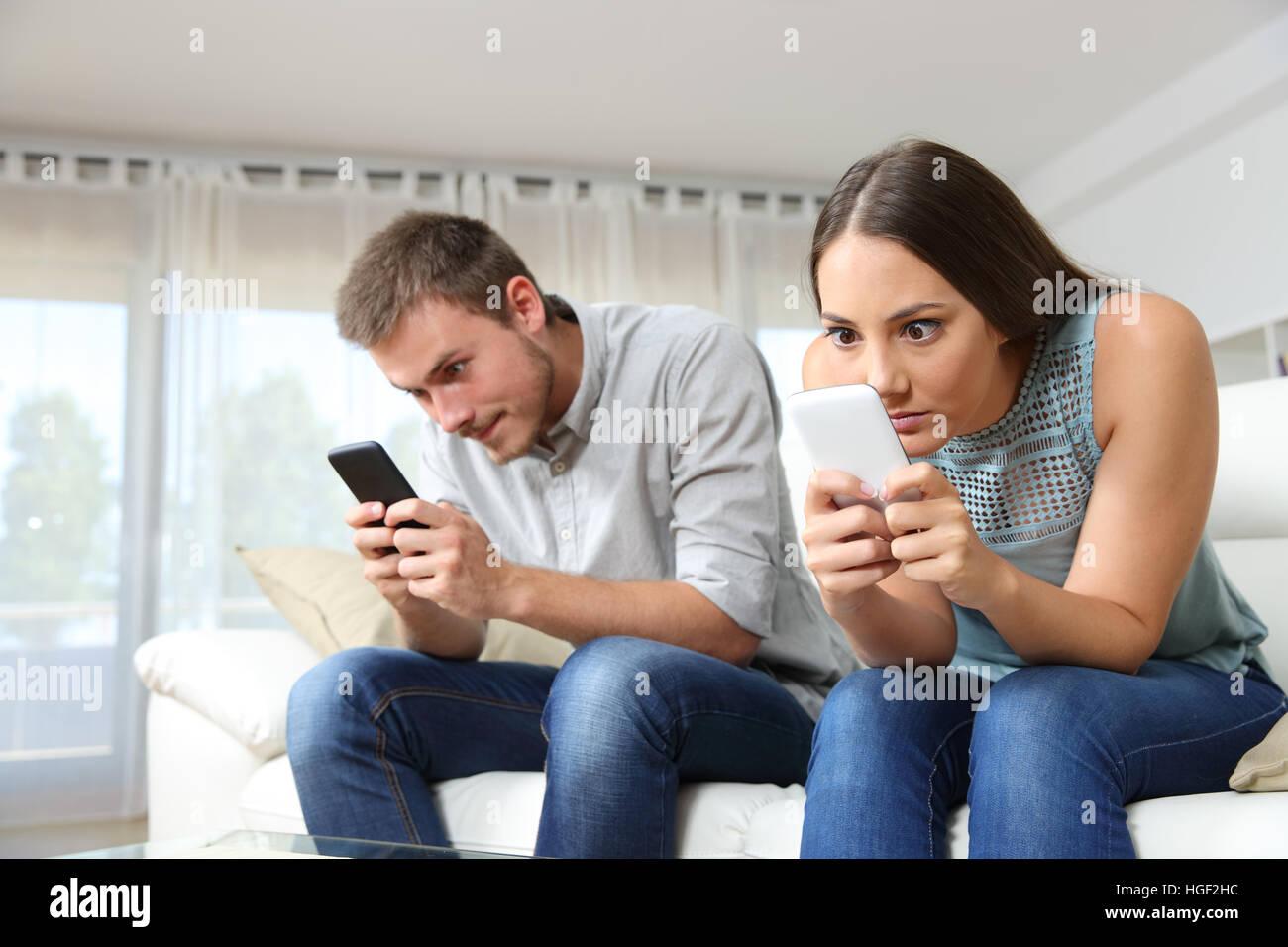 Couple d'annonces d'obsédé avec leurs téléphones intelligents en ignorant l'autre Photo Stock