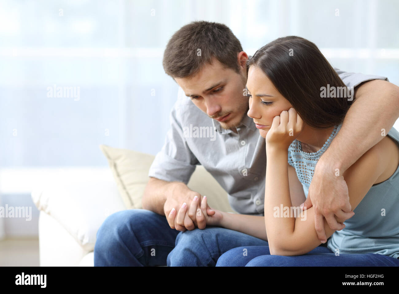 Couple triste réconfortant les uns les autres assis sur un canapé dans la salle de séjour à Photo Stock