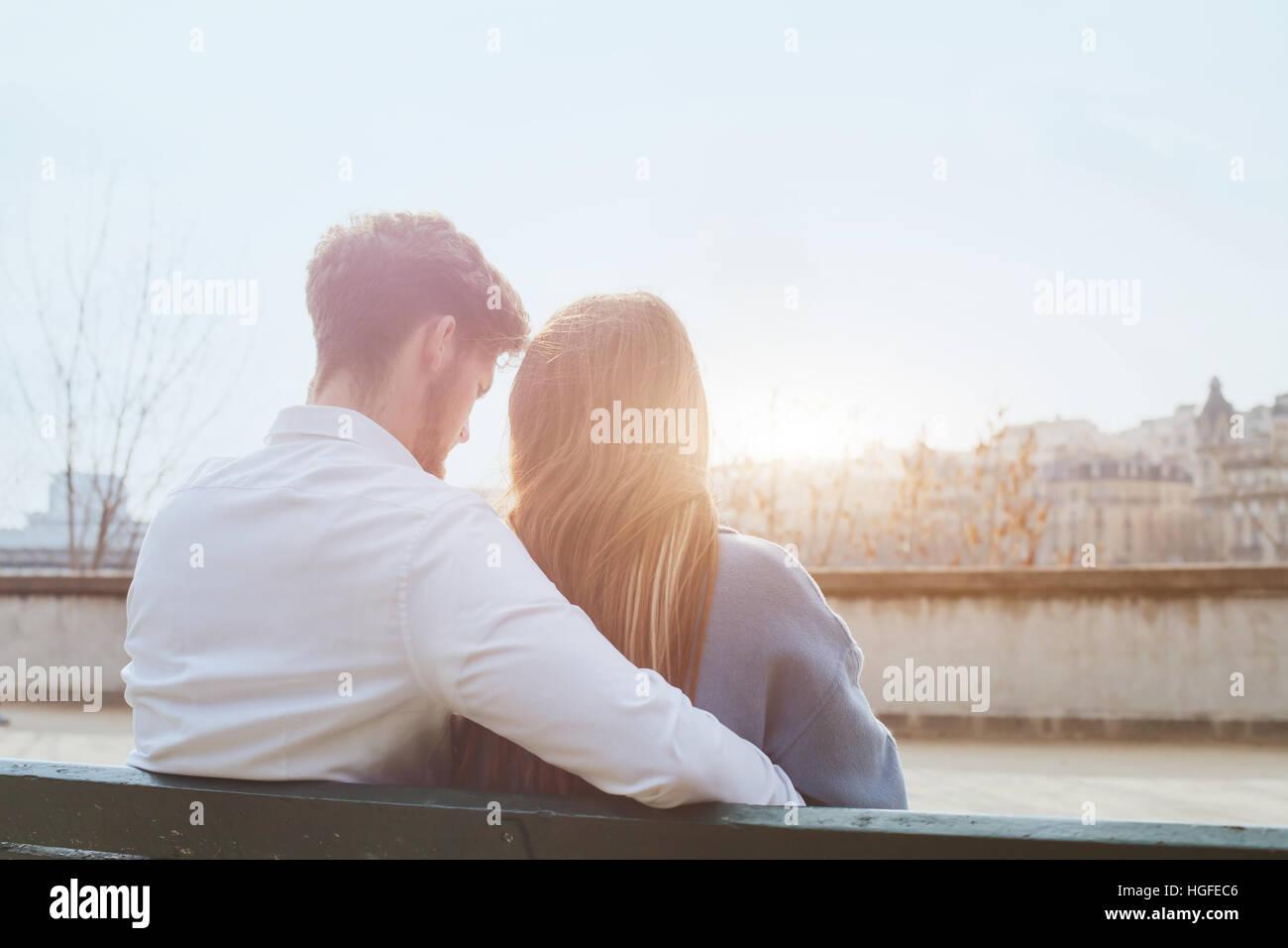 Dating ou premier amour, jeune couple assis ensemble sur le banc, vue par l'arrière Photo Stock