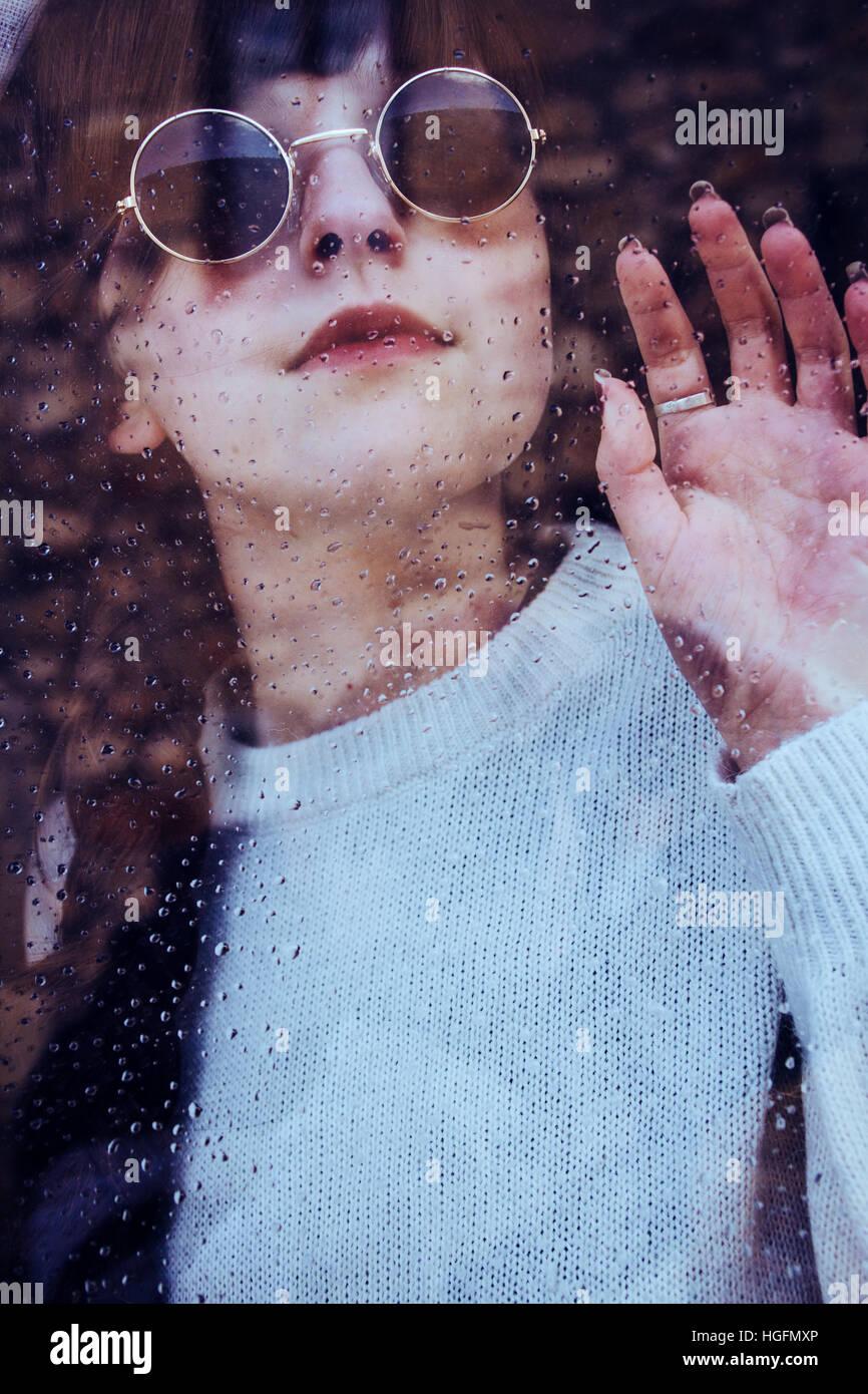 Portrait d'une jeune femme dans un jour de pluie au travers d'une fenêtre Photo Stock