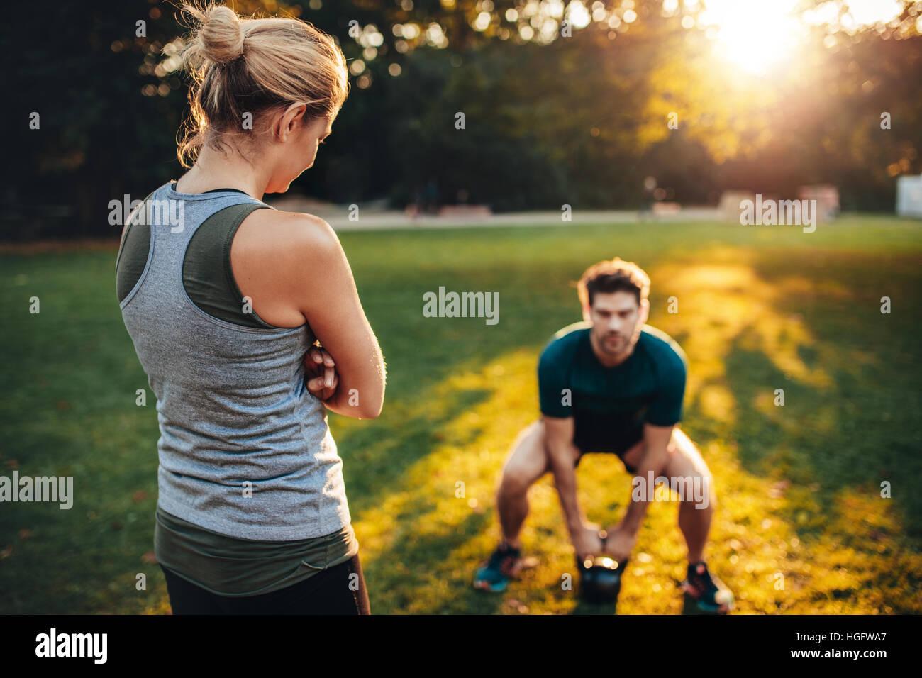 Femme trainer dans le parc et un jeune homme faisant la formation de poids avec kettlebell en arrière-plan. Photo Stock