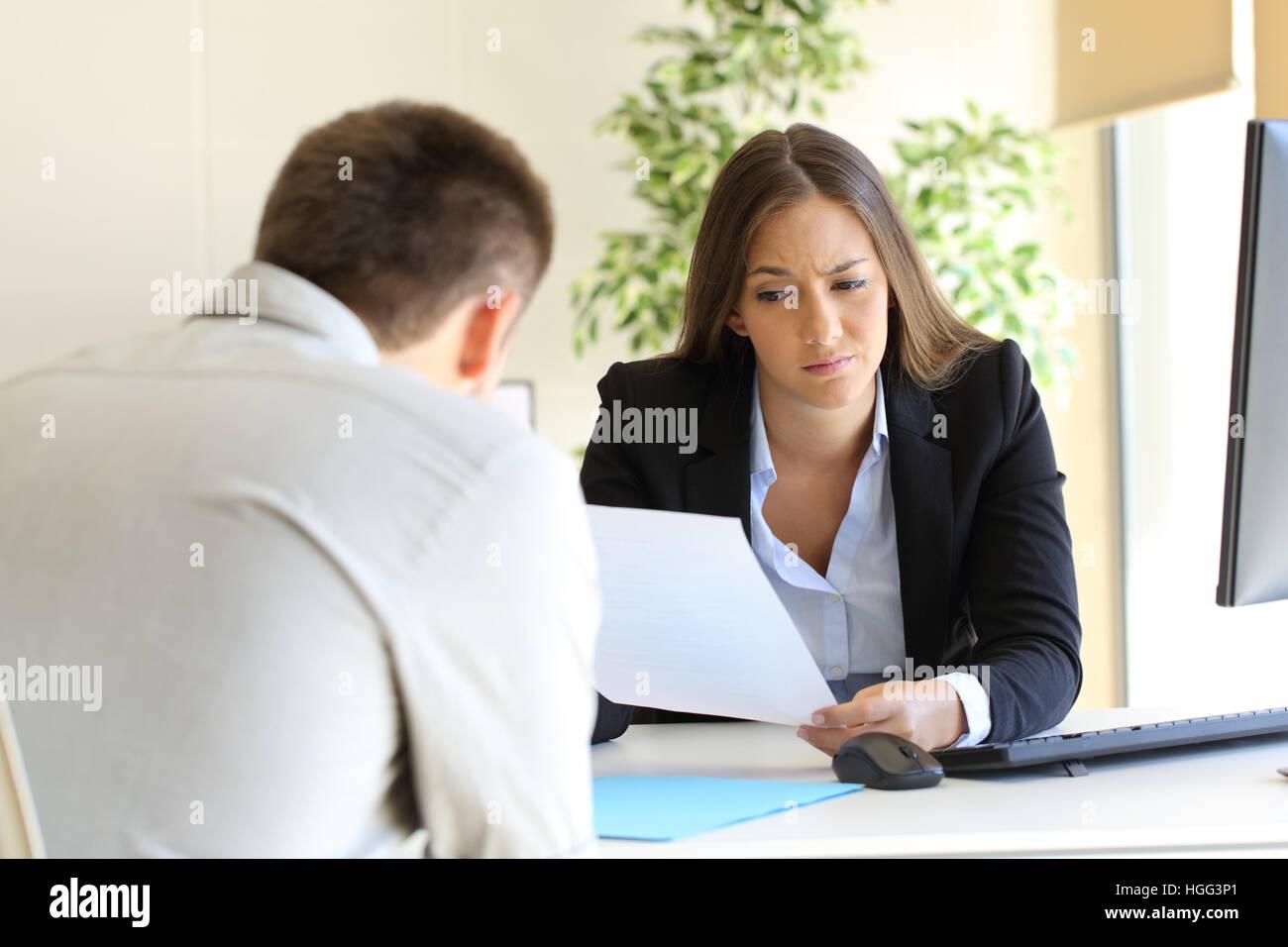 Businesswoman reading un mauvais cv dans une entrevue d'emploi Photo Stock