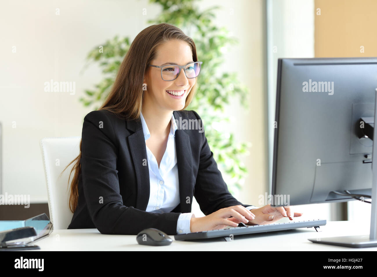 Businesswoman wearing glasses travaillant avec un ordinateur de bureau au bureau Photo Stock