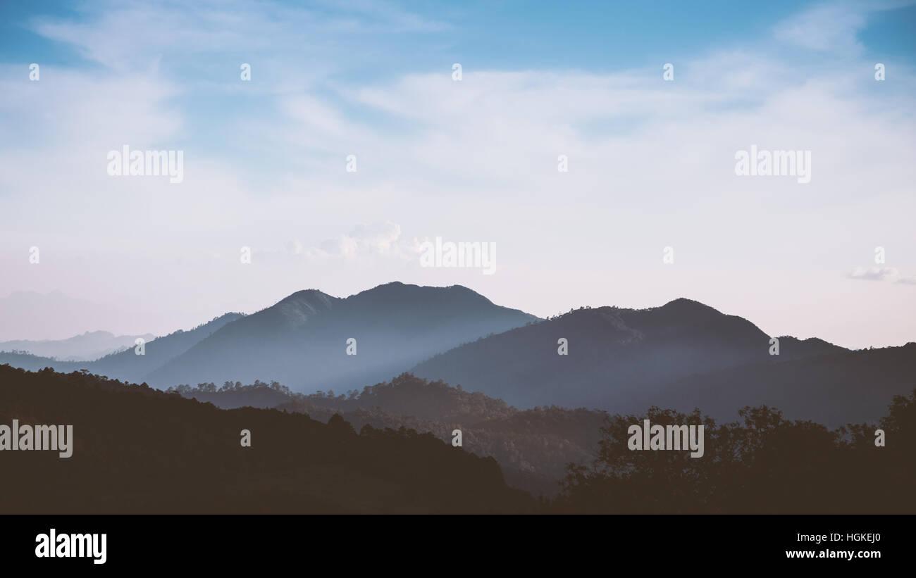 Foggy Mountain range en basse Tonalité des touches avec ciel nuageux ciel bleu Banque D'Images