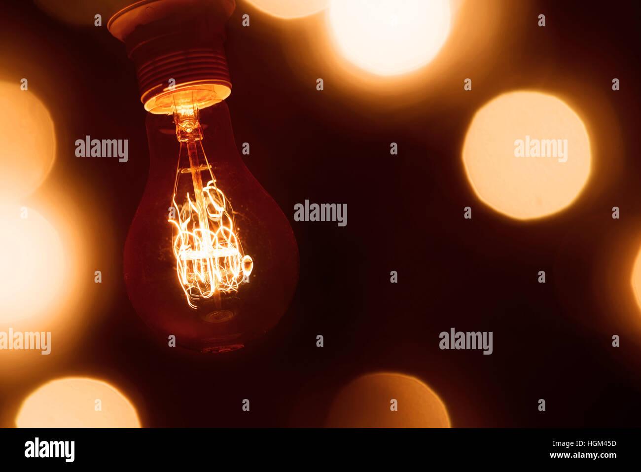 Ampoule à incandescence vintage lumineux orange foncé sur arrière-plan flou Photo Stock