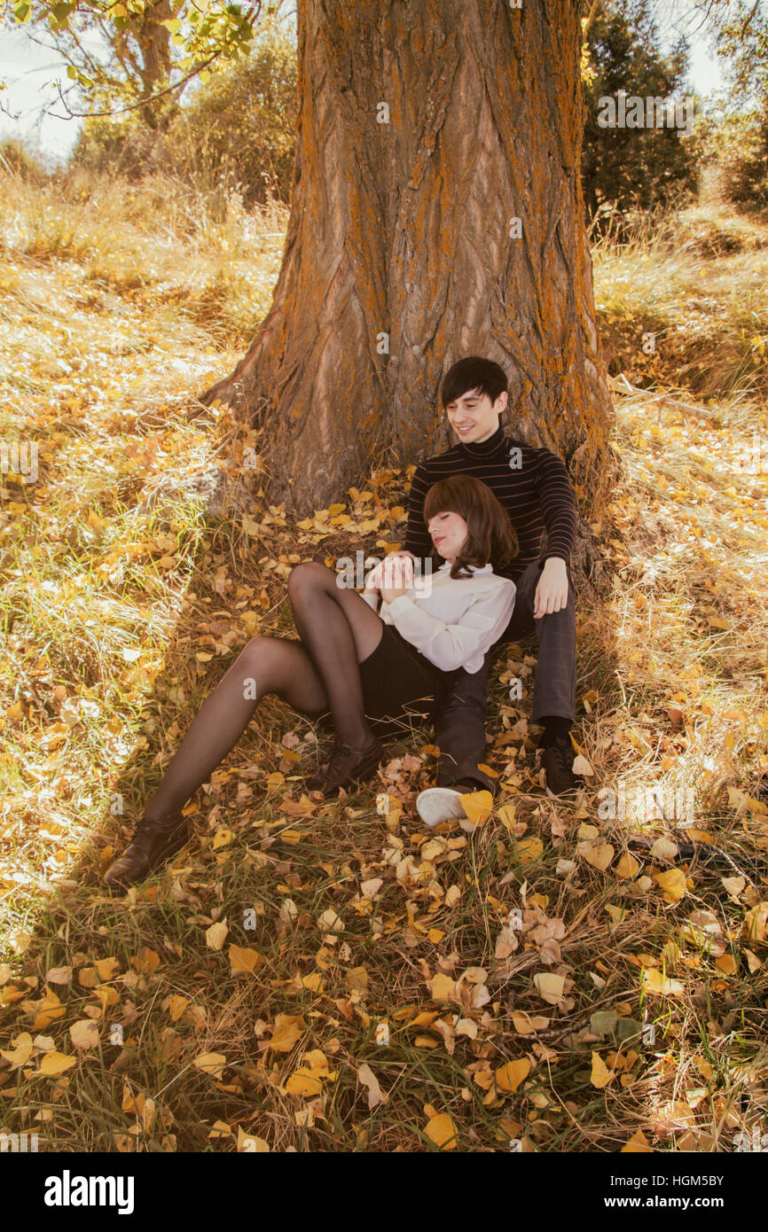 Jeune couple dans un parc en automne, s'appuyant sur un arbre Photo Stock