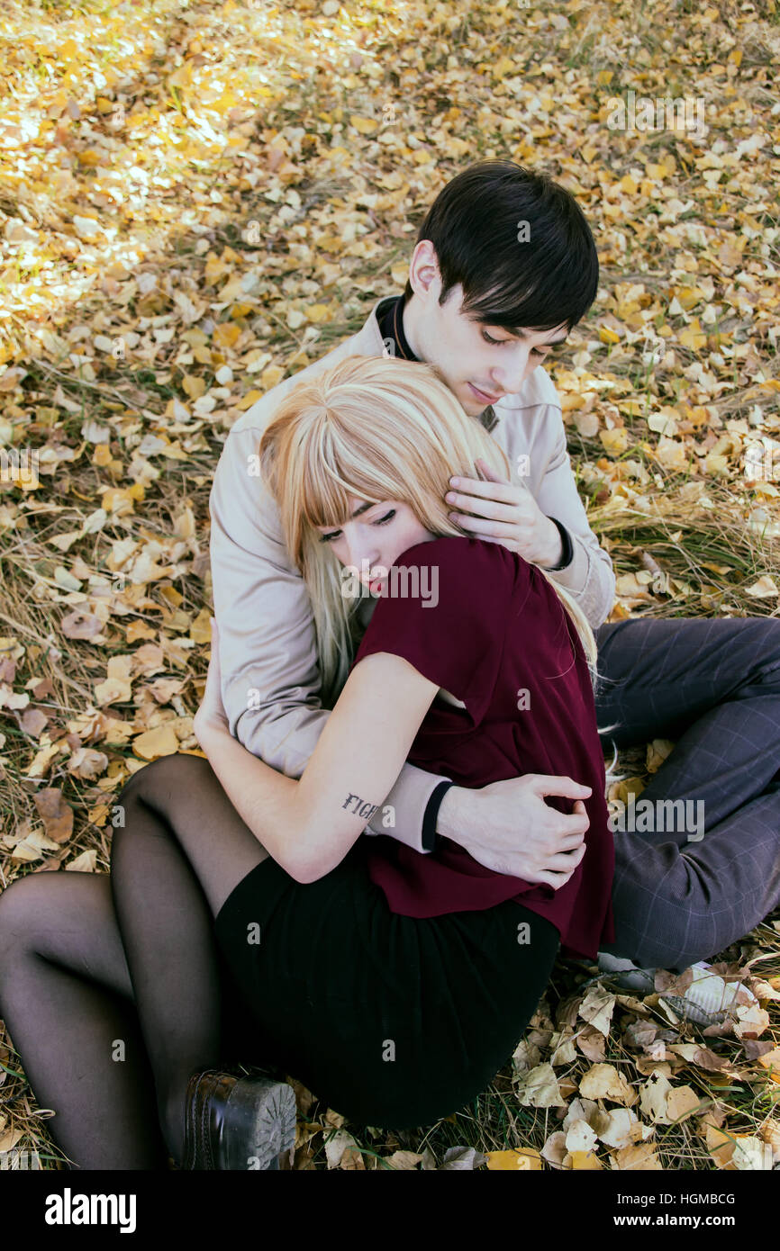 Jeune couple hugging mutuellement dans un parc en automne Photo Stock