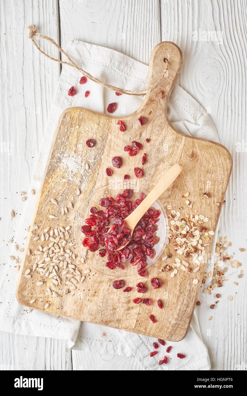 Les canneberges sèches avec des céréales sur la table en bois blanc Vue de dessus Photo Stock