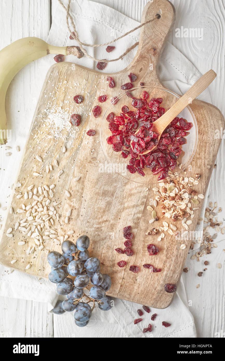 Canneberges séchées, des céréales et des fruits sur la table en bois blanc Vue de dessus Photo Stock