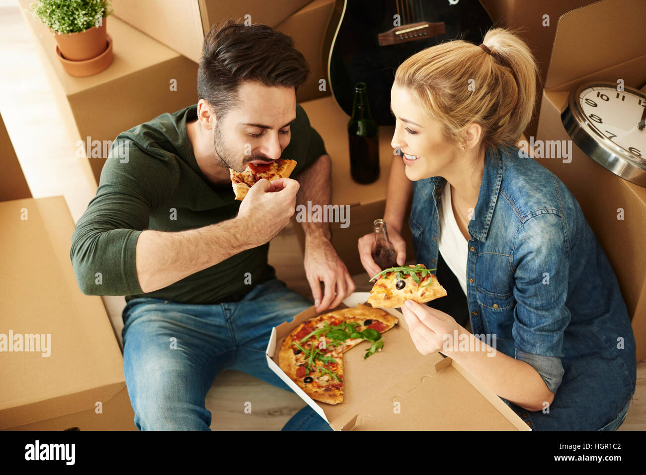 Déménagement chambre couple eating pizza Photo Stock
