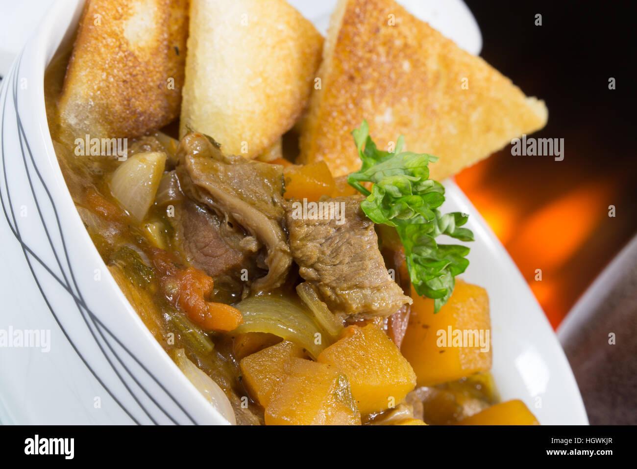 Un pub anglais/restaurant bol de goulasch de Bœuf servi avec des croûtons de pain frit. Banque D'Images