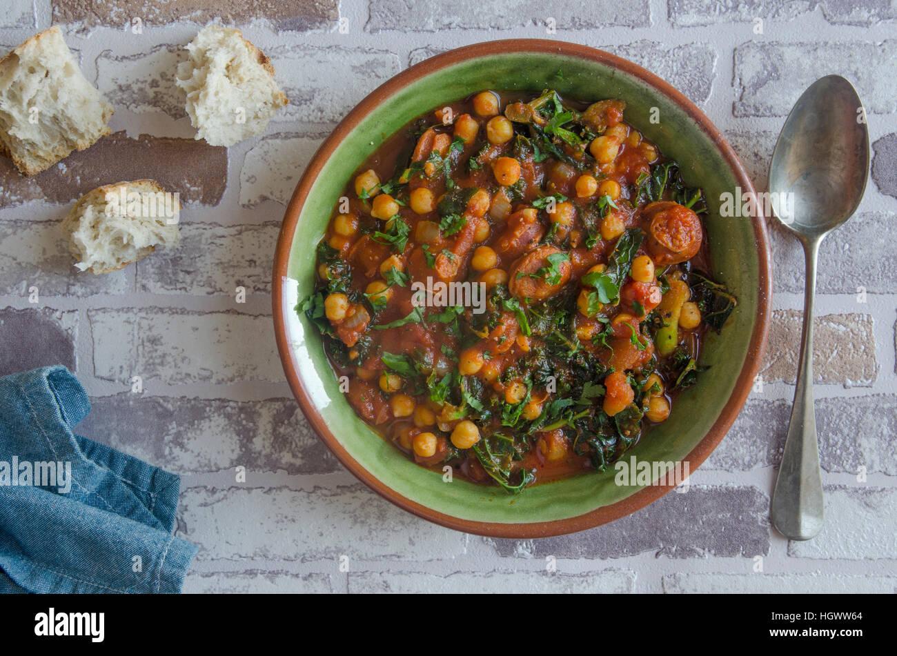 Le pois chiche, chorizo et kale ragoût avec pain rustique Photo Stock