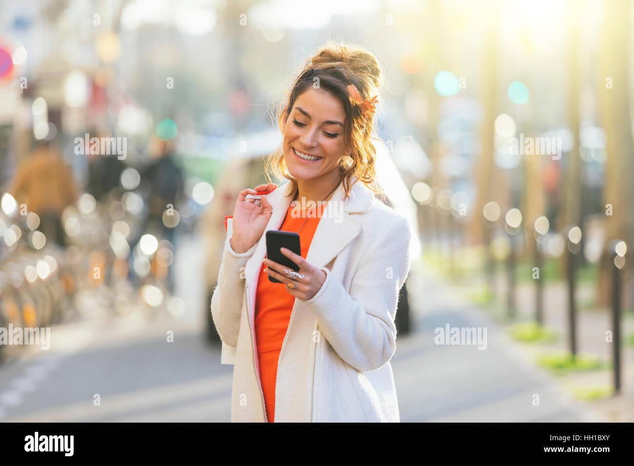 Paris, femme à l'aide de smart phone in street Photo Stock
