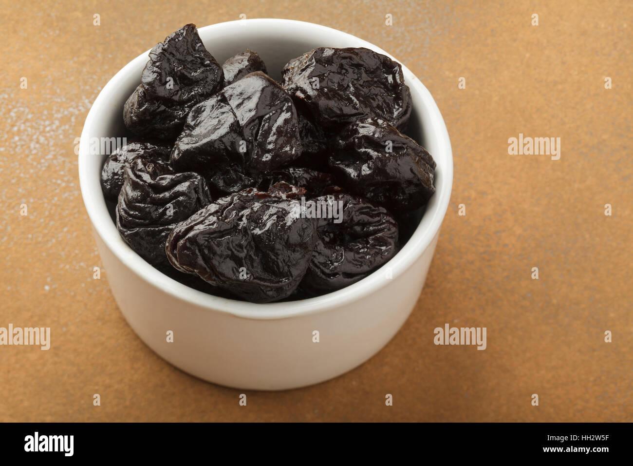 Les pruneaux dans un bol blanc Photo Stock