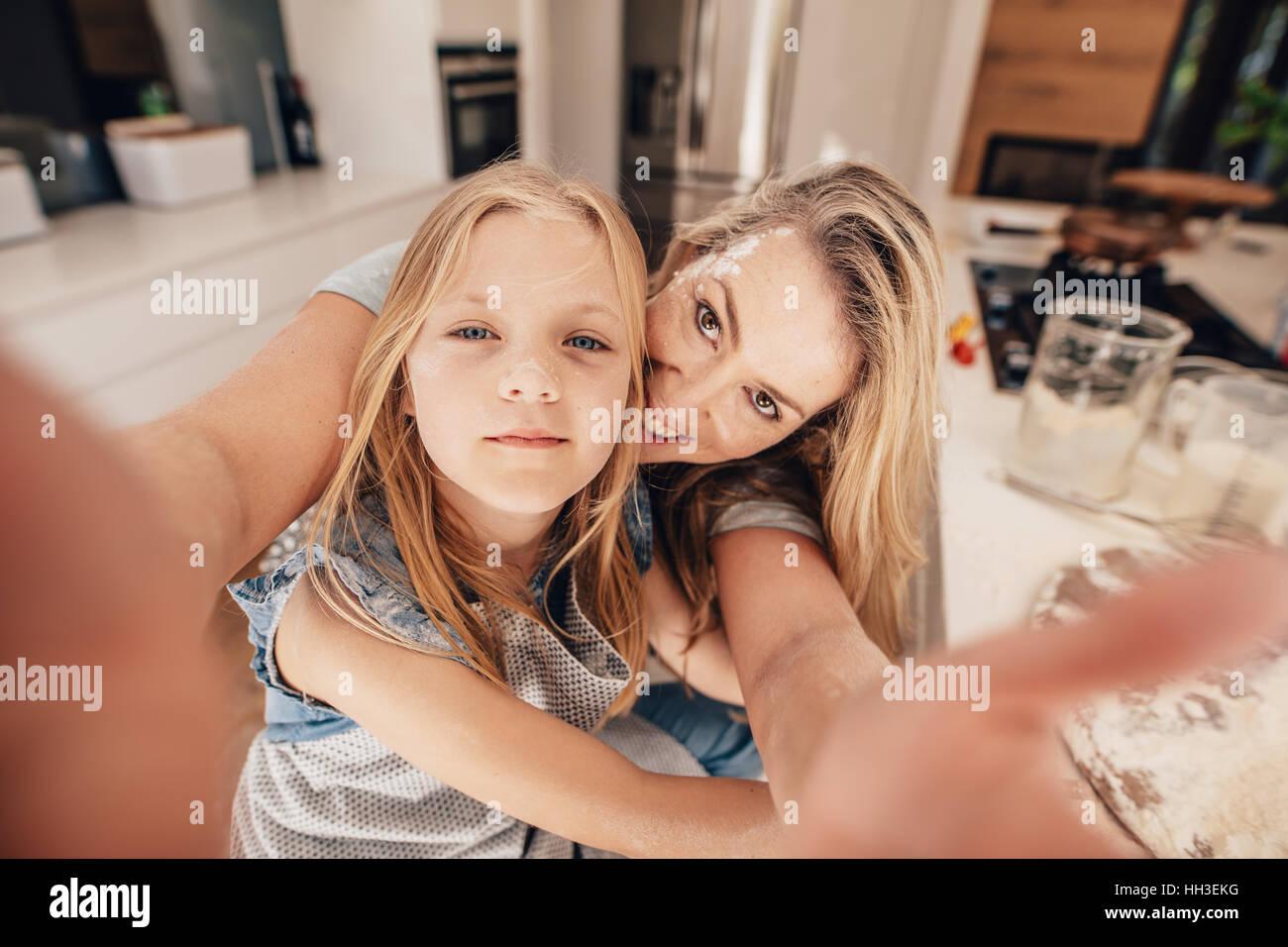 Happy woman and girl prenant un. selfies Les deux dans la cuisine avec la mère tenant un téléphone Photo Stock