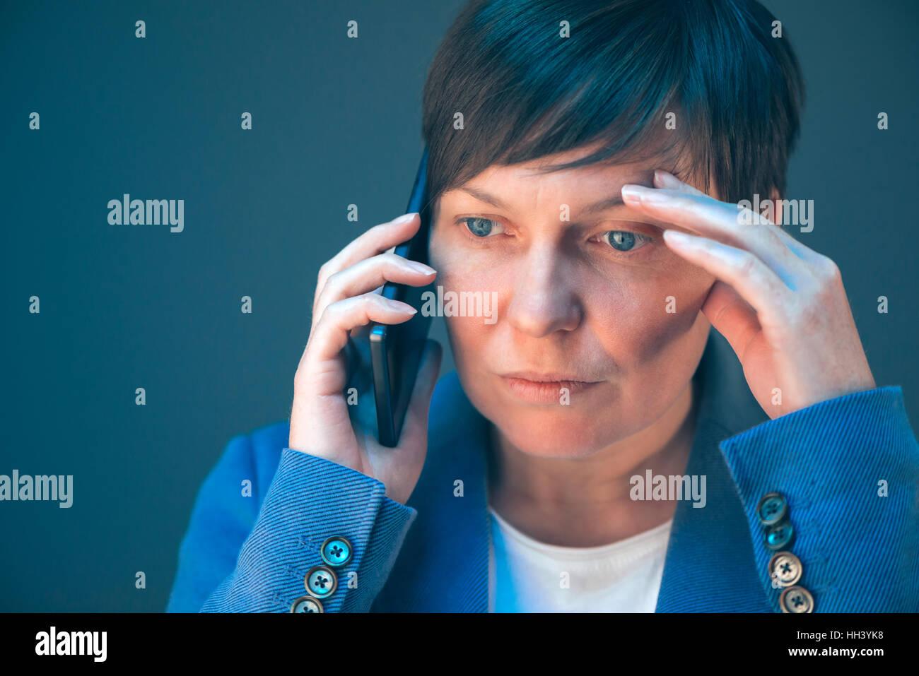 Femme d'inquiets nerveux lors d'un entretien téléphonique avec un désagréable téléphone Photo Stock