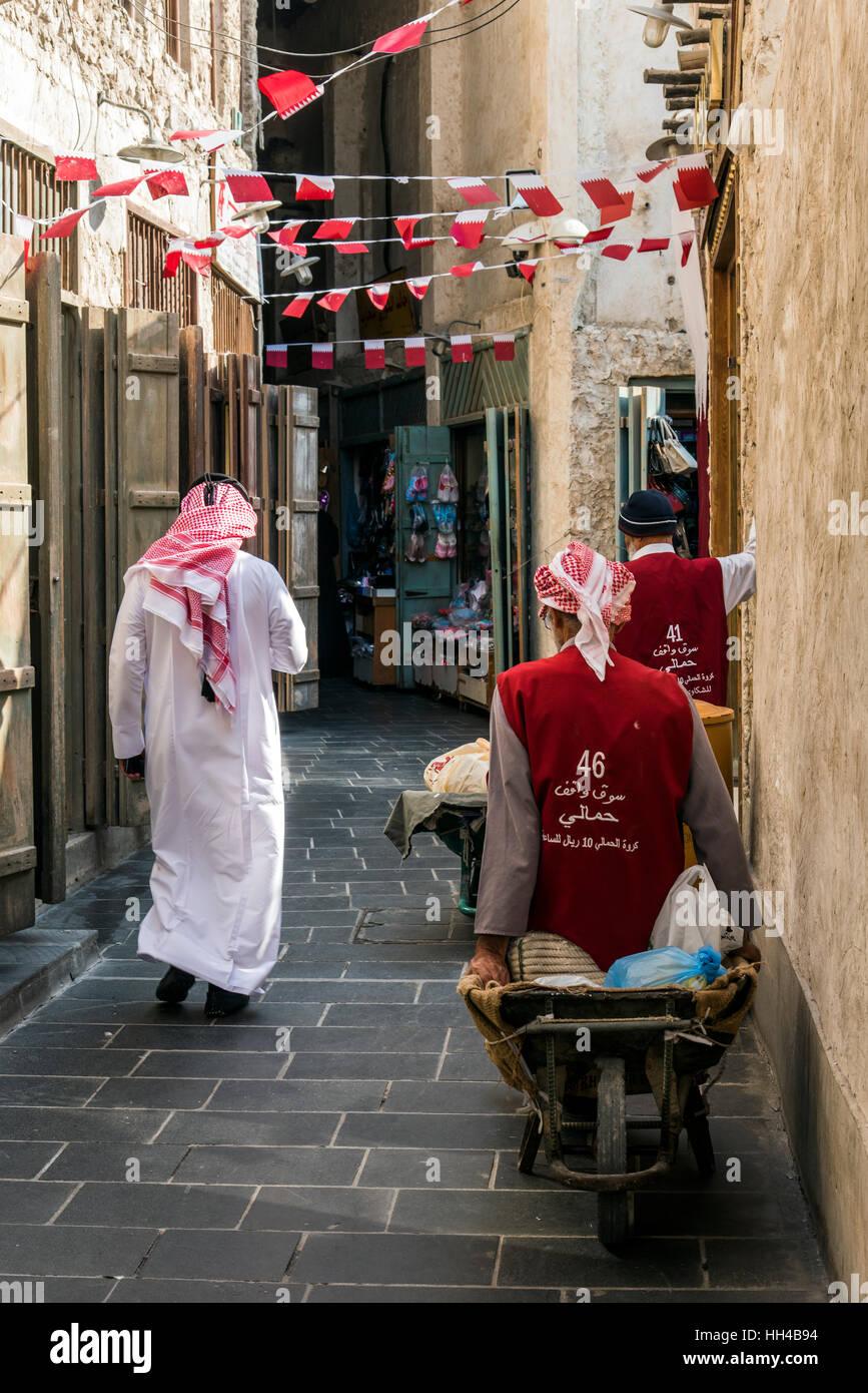 Habillé traditionnellement arabe marche dans le Souq Waqif, Doha, Qatar Photo Stock