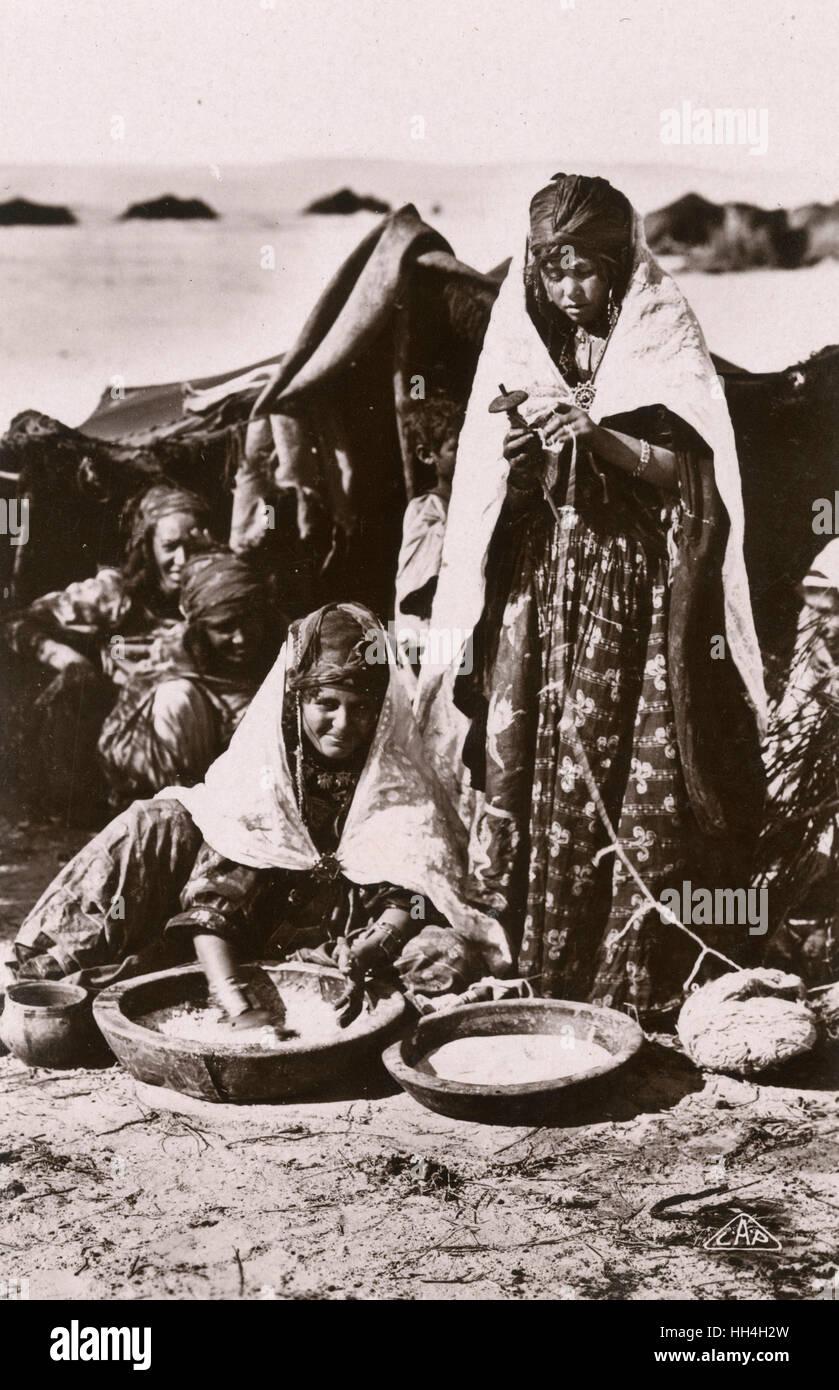 Algérie - les femmes nomades effectuant des tâches à l'extérieur du textile et la cuisine de leur tente. Banque D'Images