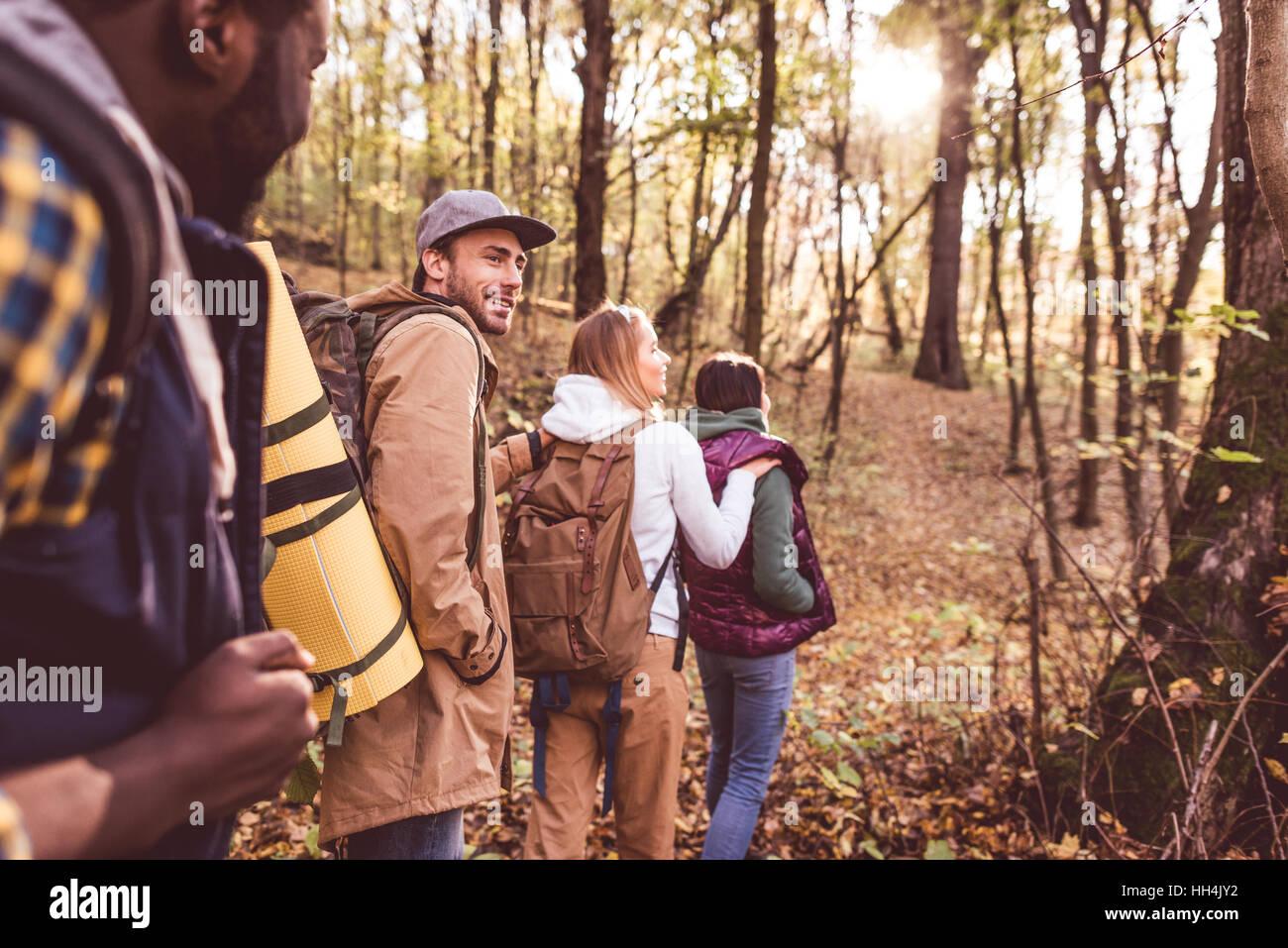 Quatre jeunes backpackers marcher dans la rangée en forêt d'automne au coucher du soleil Photo Stock