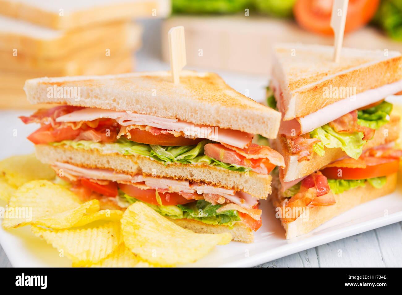 Un club sandwich sur une table rustique dans une lumière vive. Photo Stock