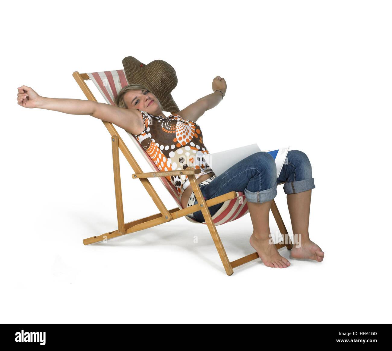 La photographie de studio d'une jeune fille blonde en relaxant la chaire de toile blanc retour Banque D'Images