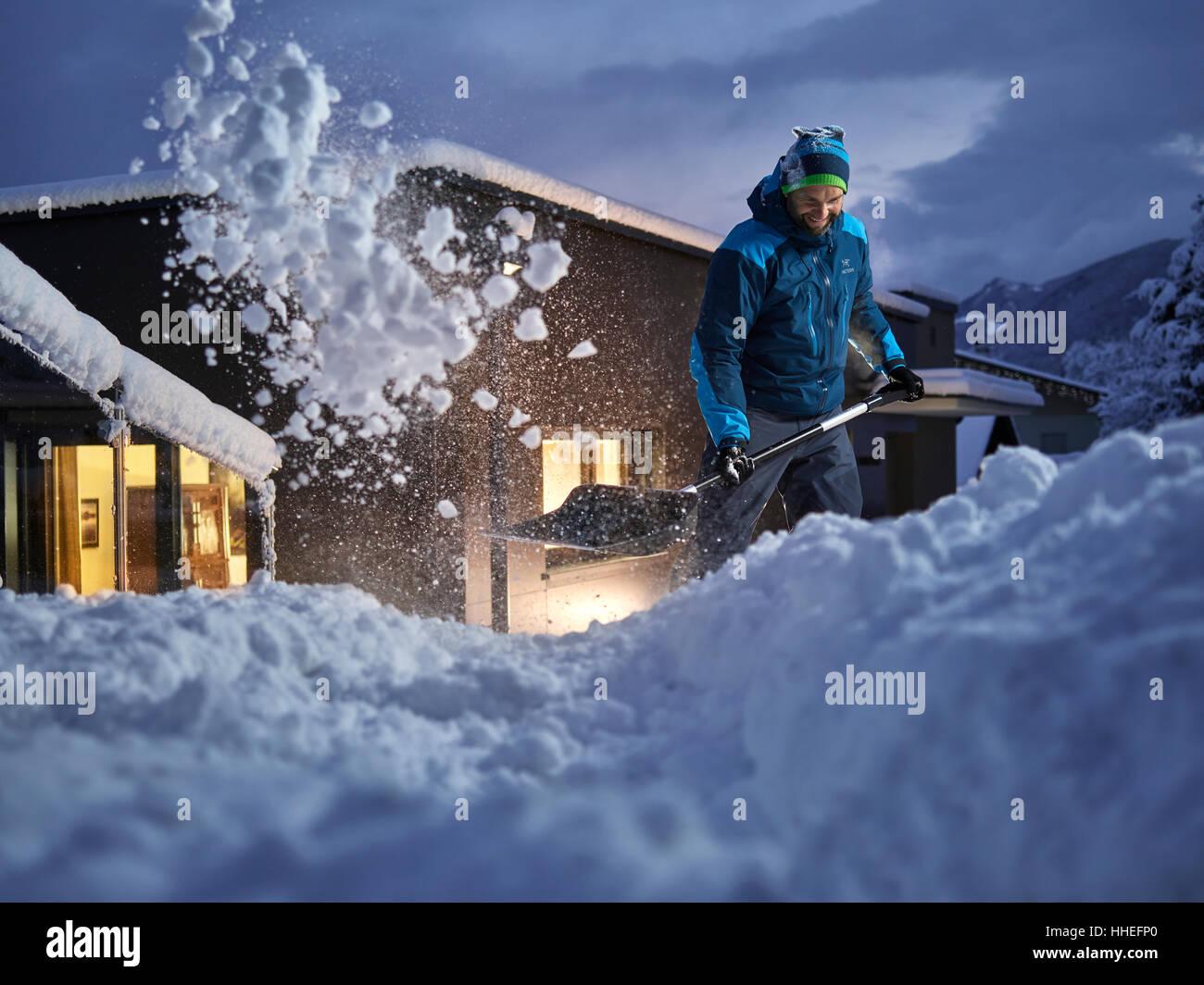 Homme, 35-40 ans, pelleter la neige au crépuscule, Kolsass, Tyrol, Autriche Photo Stock