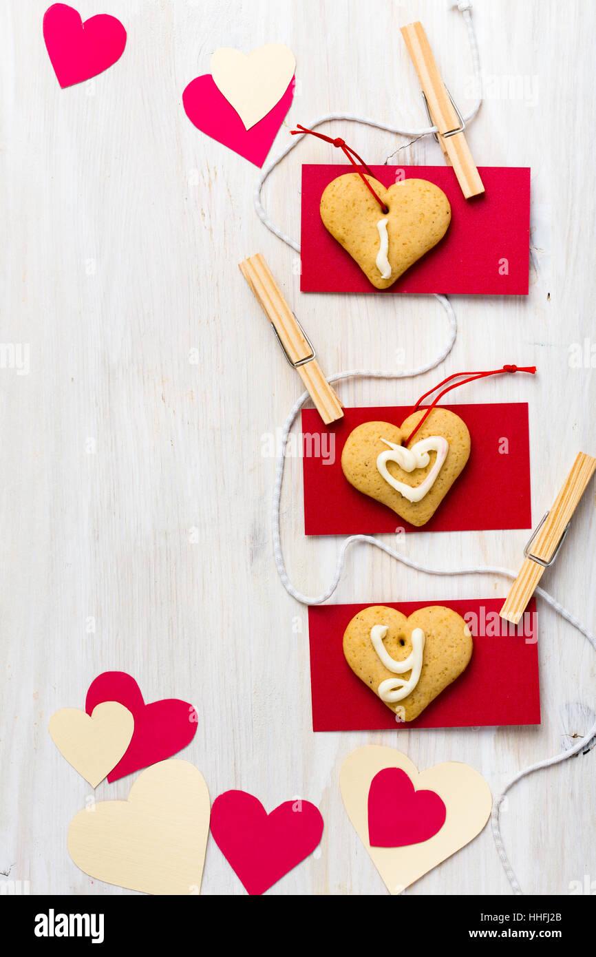 Coeurs de papier et les cookies en forme de coeur suspendu à une chaîne avec les mini épingle à linge blanc sur Banque D'Images