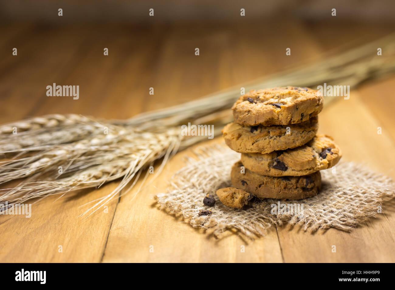 Les cookies au chocolat sur un sac en tissu sur bois. Cookies aux pépites de chocolat et de malt de riz tourné Photo Stock