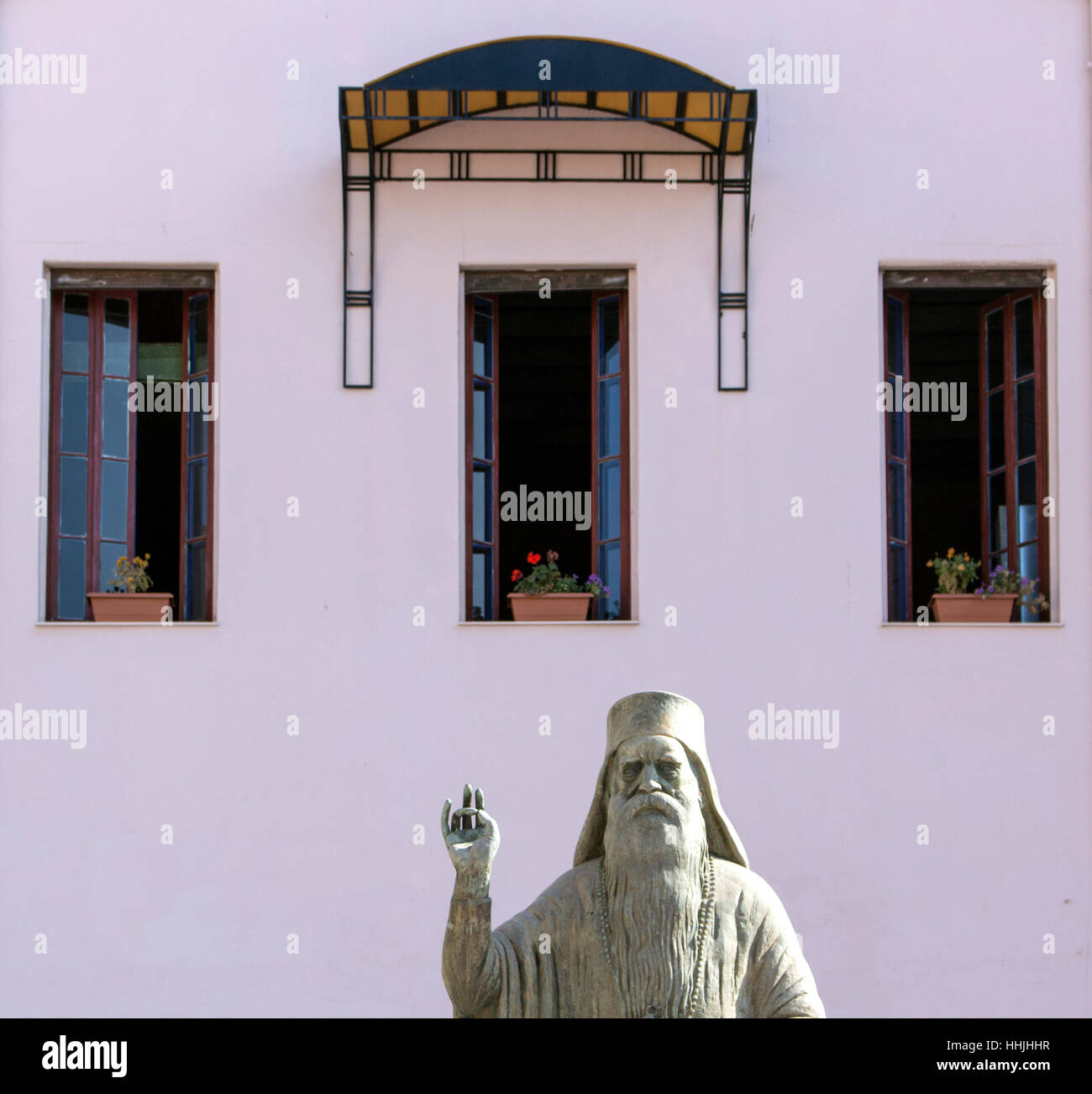 Statue avec main levée et trois doigts vers le haut trois fenêtres Photo Stock
