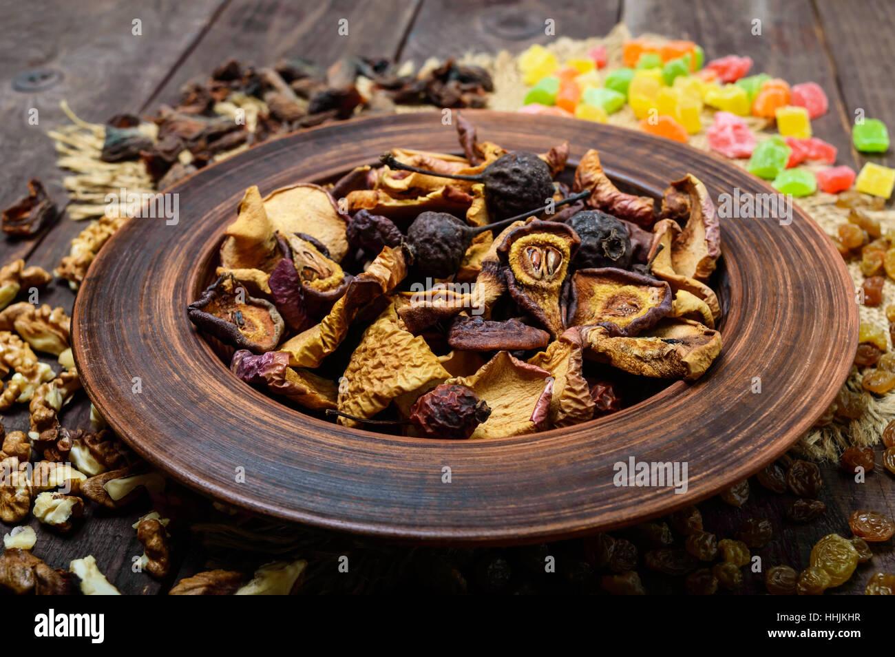 Fruits secs (pommes, poires, abricots), les petits fruits, les raisins secs et les noix dans un bol sur fond de Photo Stock