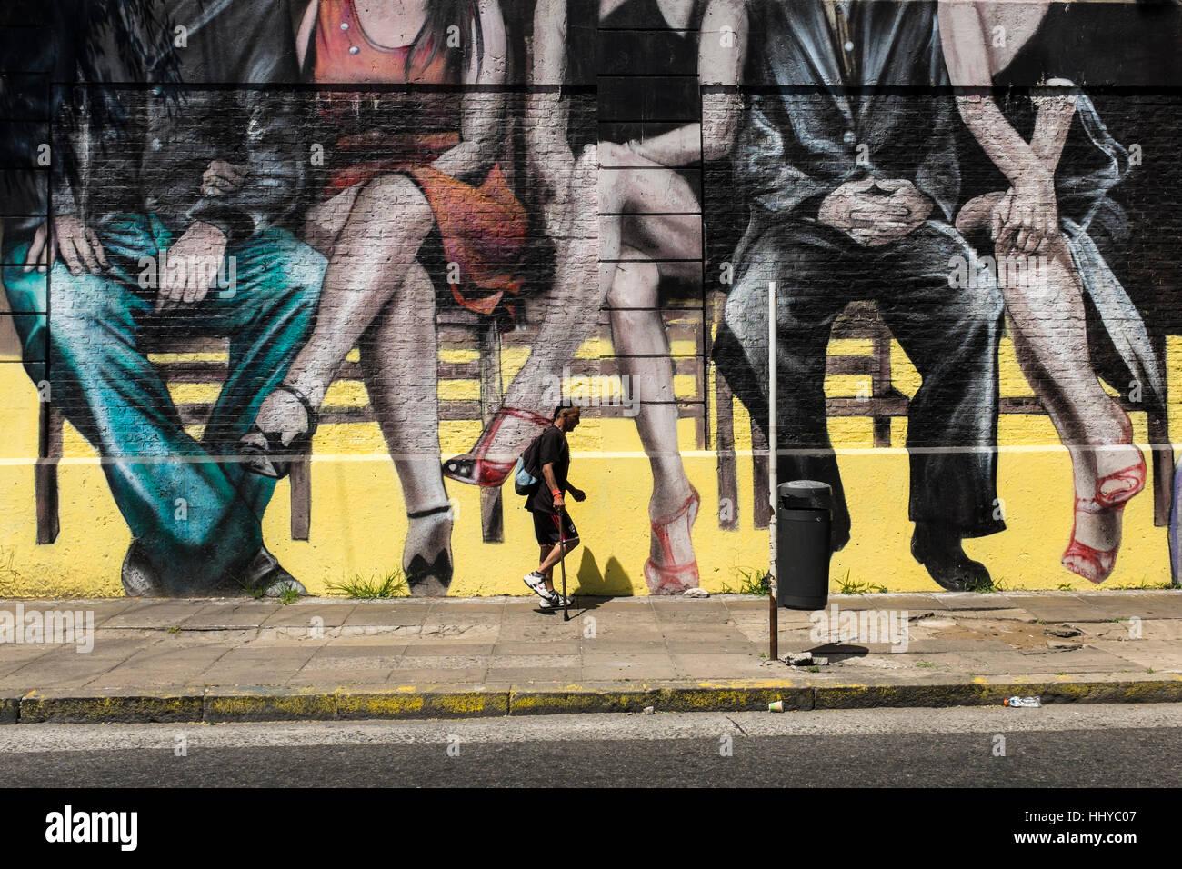En passant devant une peinture murale représentant la ville assis des couples, Buenos Aires, Argentine Photo Stock
