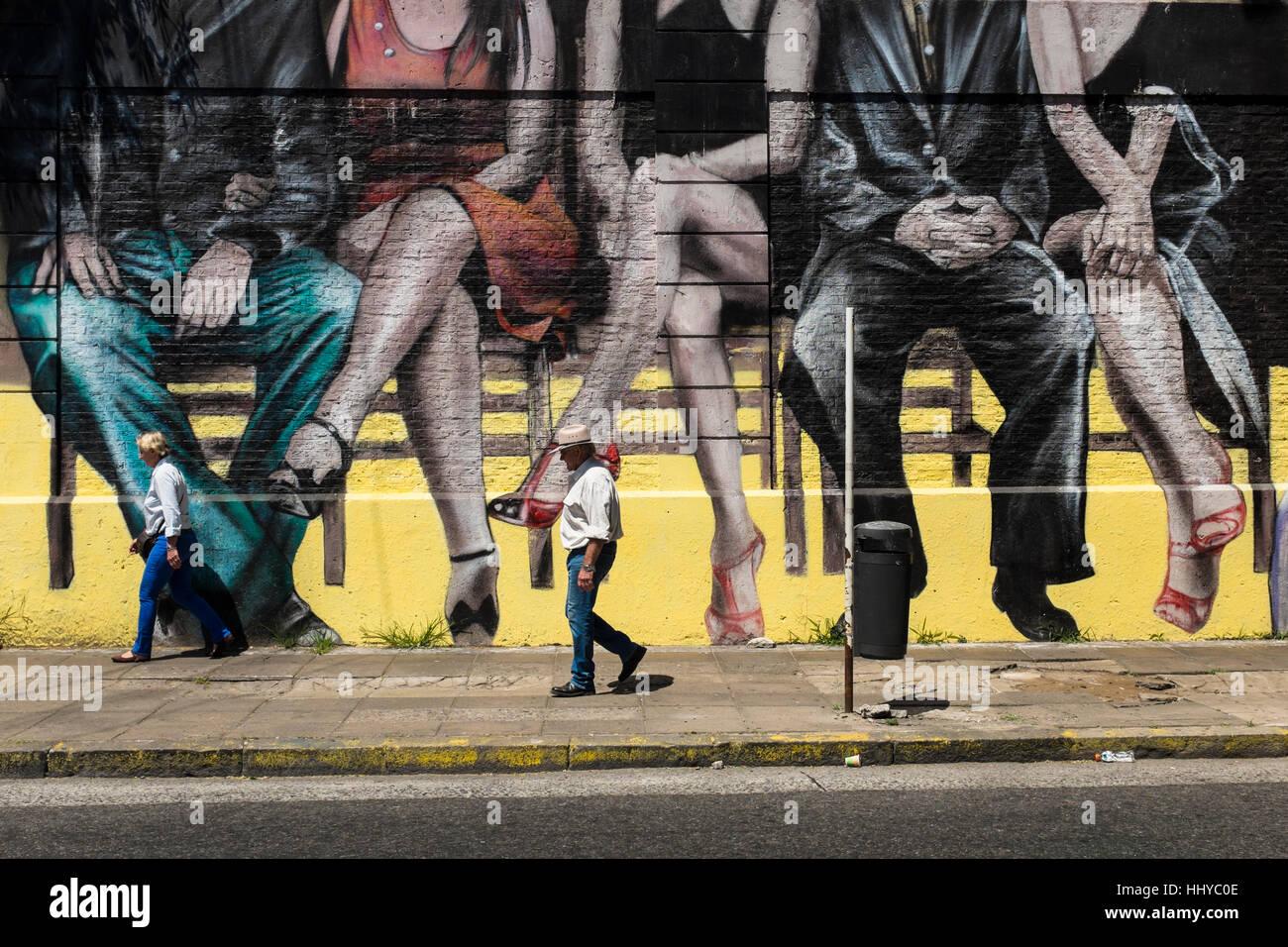 En passant devant une peinture murale représentant la ville de Buenos Aires, des couples assis Photo Stock