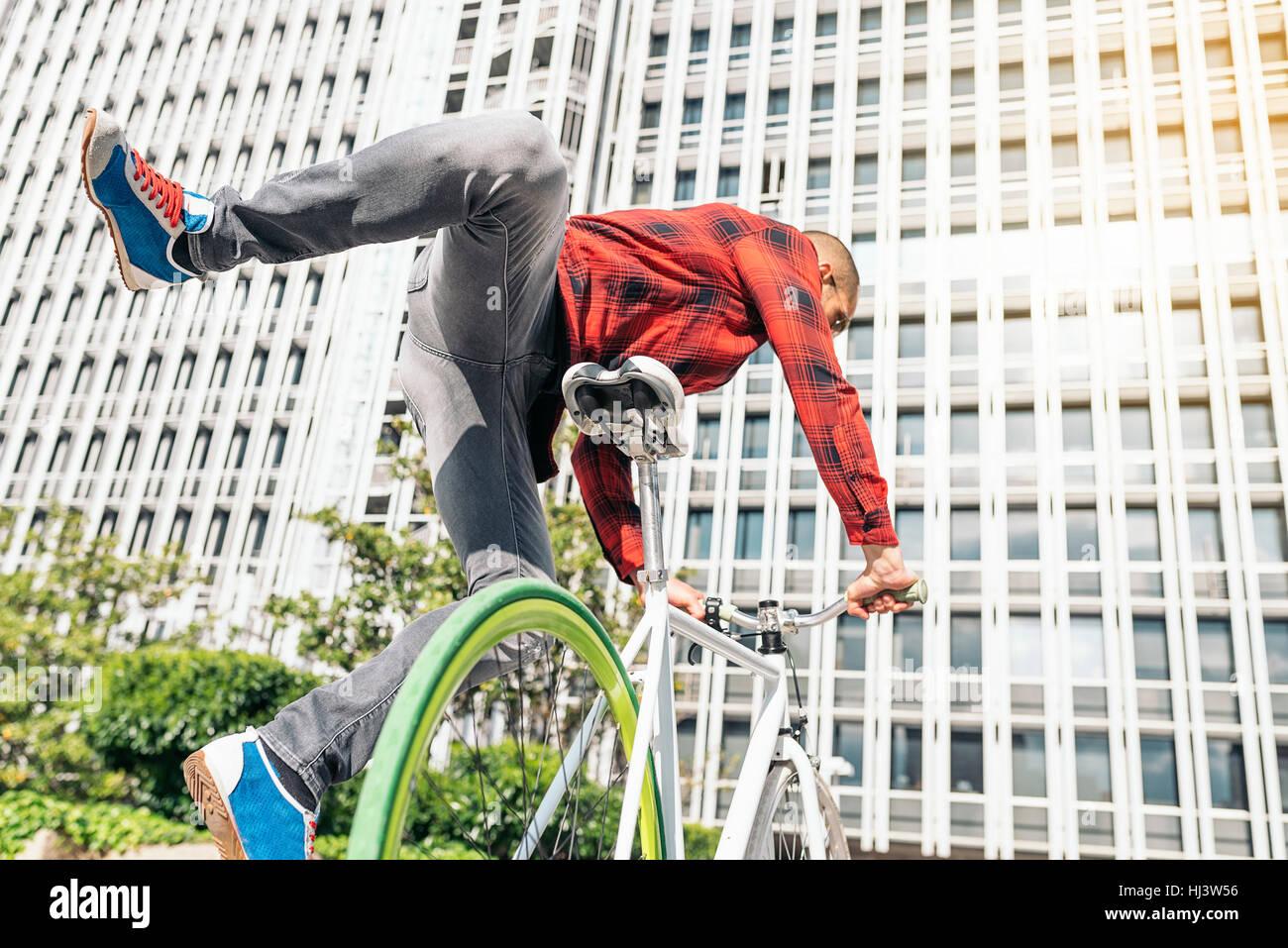 Beau jeune homme sur le vélo dans la ville. Location conceptBanque D'Images
