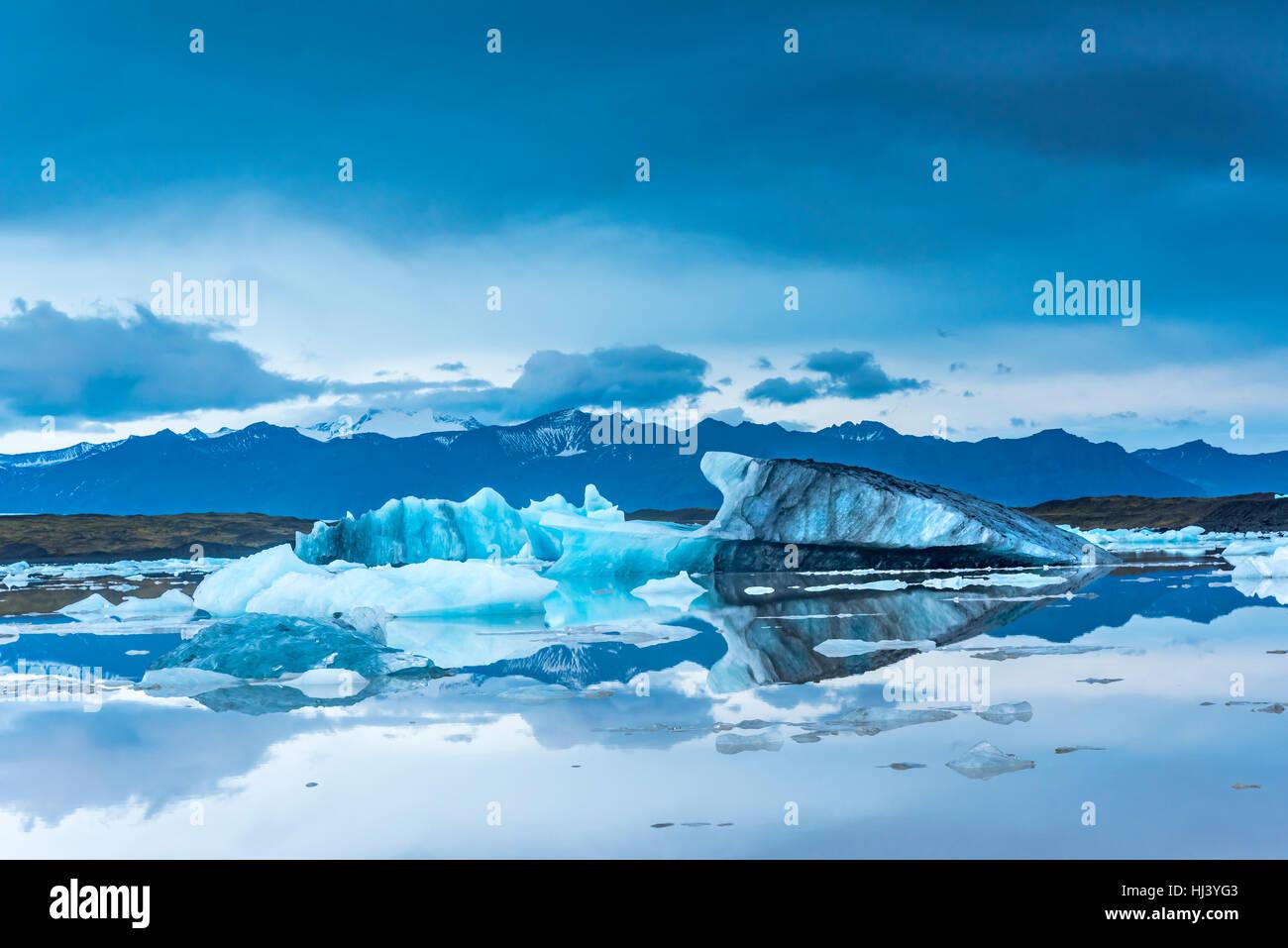 Les icebergs le long de la rive du Jokulsarlon glacial lagoon pendant un temps couvert bleu reste immobile tandis Banque D'Images