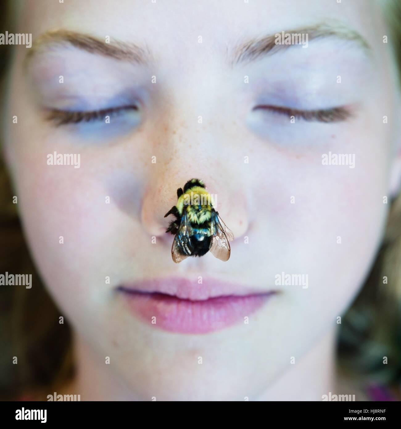 Fille avec une abeille sur son nez Photo Stock