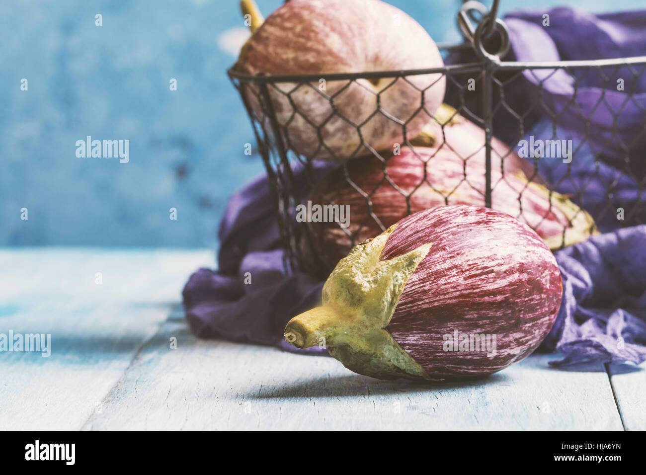 Variétés d'aubergine dans panier métal sur fond bleu. Banque D'Images