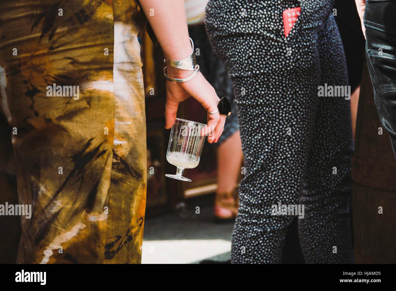 Partie inférieure d'une femme avec un verre de vin dans une partie en plein air. Photo Stock