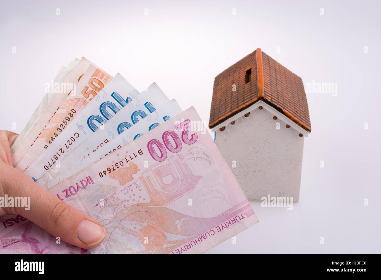 Main tenant Livre turque billets par le côté d'un modèle de maison sur fond blanc Photo Stock