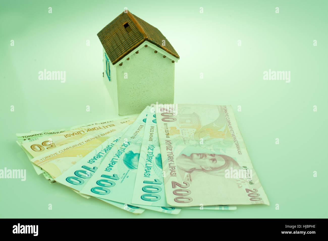 Billets Lire turque par le côté d'un modèle de maison sur fond blanc Photo Stock
