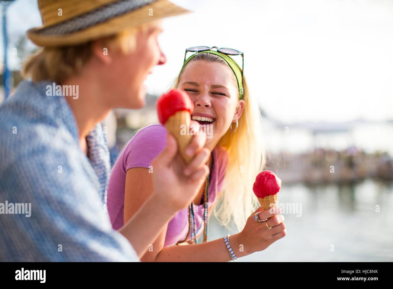Jeune couple de rire et de manger des glaces sur le bord de mer, Majorque, Espagne Photo Stock