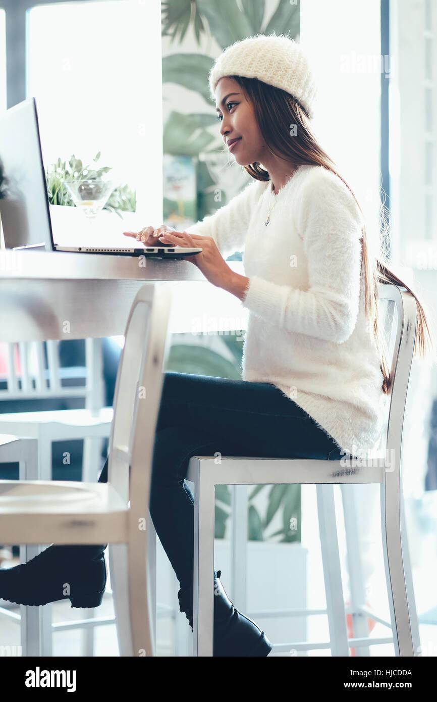 Belle fille en réseau dans un café avec un ordinateur portable Photo Stock