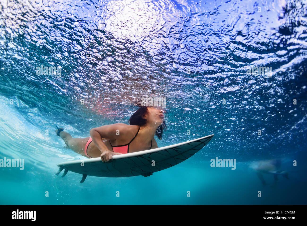 Active girl en action. Femme avec surfeur surf board sous-marine Plongée en vertu de briser l'eau des vagues d'océan, Banque D'Images