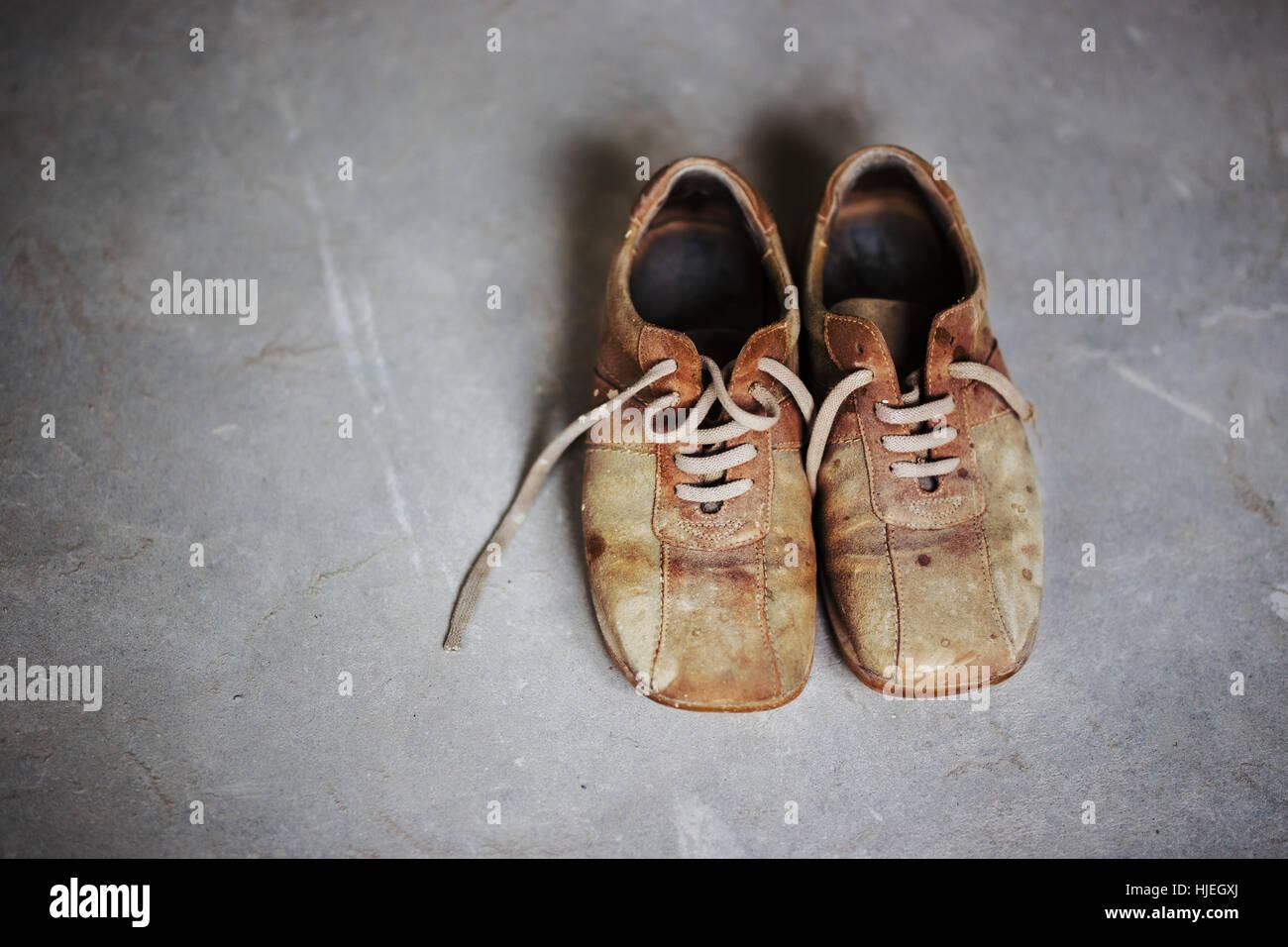 Old grunge marron bottes sur fond de ciment gris Photo Stock