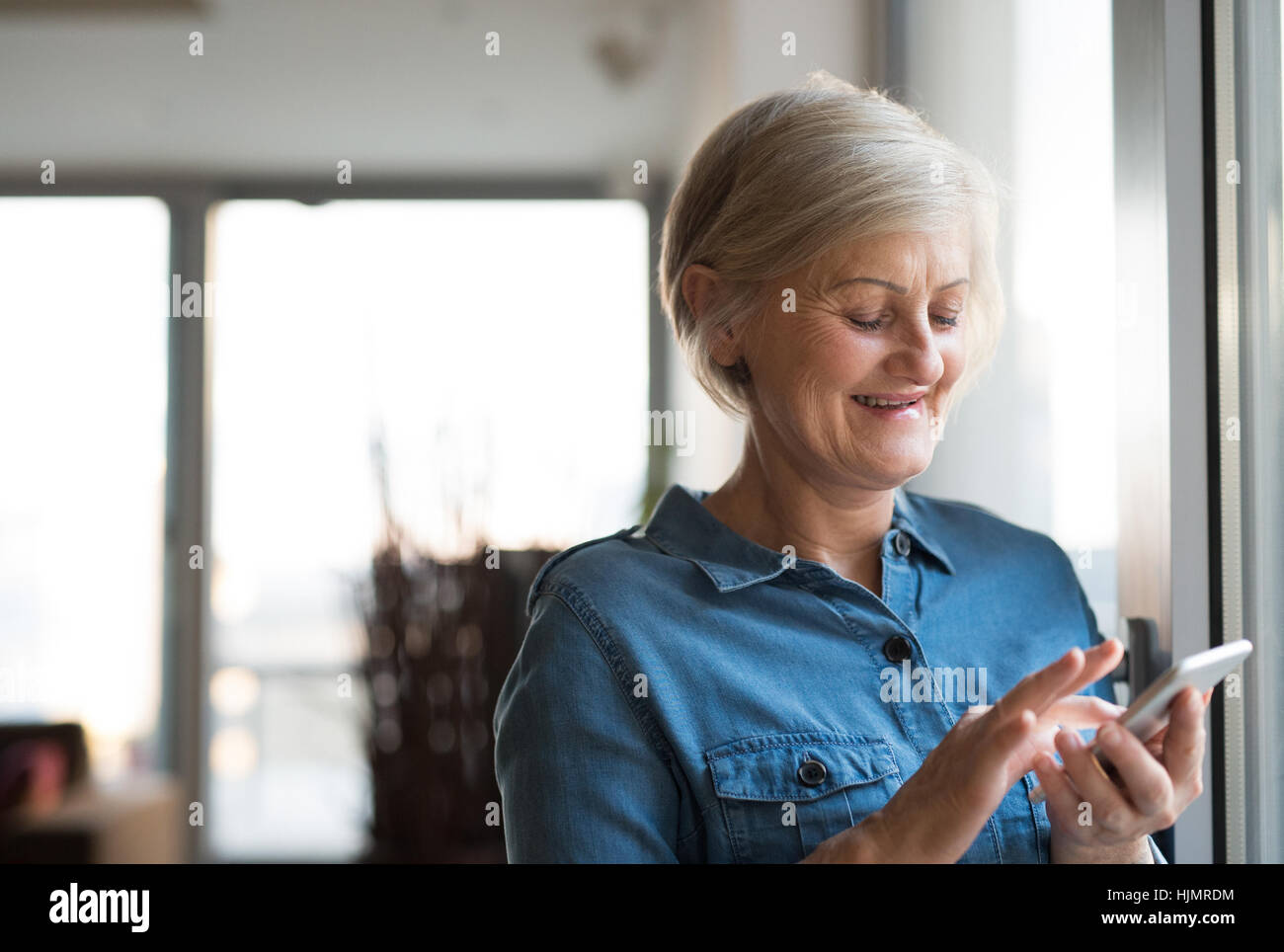 Senior woman with smartphone à la maison debout à la fenêtre Photo Stock
